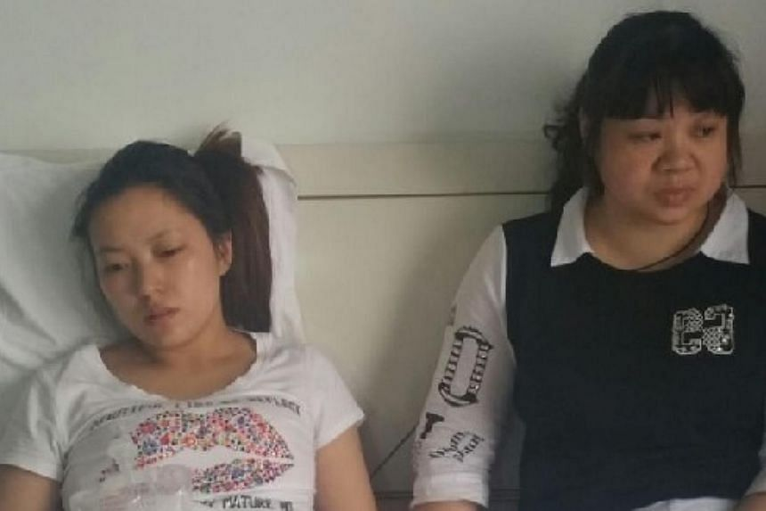 Ms Tan Mei (left) and Ms Chen Jian, wife and sister of missing crew member Chen Bo, 33, await news at a hotel in Jianli county, Hubei province. -- PHOTO: KOR KIAN BENG