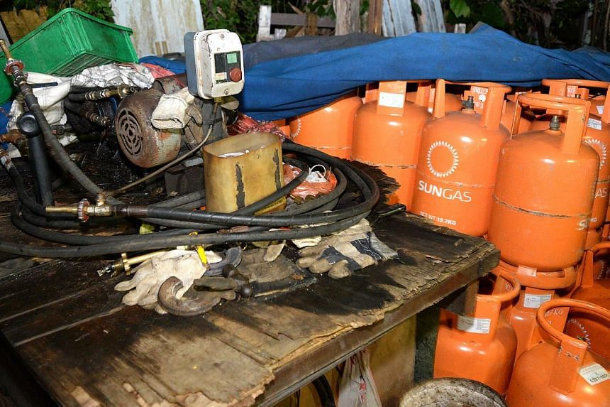 A makeshift factory suspected to be illegally refilling LPG (liquefied petroleum gas) canisters was discovered in a forest clearing in Seletar West on June 2, 2015. -- PHOTO: SHIN MIN