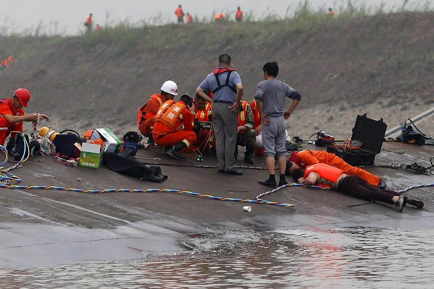 Rescuers listen for reactions from inside a sunken ship as they search for survivors at the Jianli section of the Yangtze River, Hubei province, China, June 2, 2015. -- PHOTO: REUTERS
