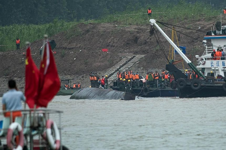"""Rescue workers are seen on the hull of capsized passenger ship Dongfangzhixing or """"Eastern Star"""" in the Yangtze river at Jianli in China's Hubei province on June 3, 2015. -- PHOTO: AFP"""