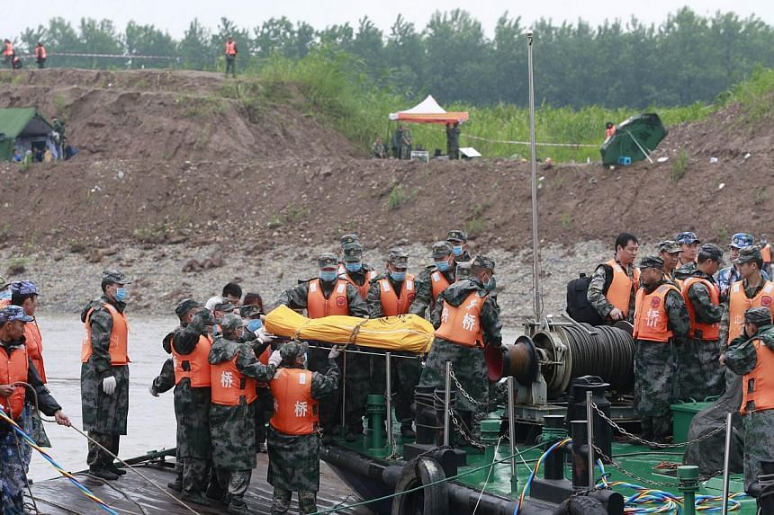 "Rescue personnel move the remains of victims who were travelling on the capsized passenger ship Dongfangzhixing or ""Eastern Star"" onto a boat in the Yangtze river at Jianli in China's Hubei province on June 3, 2015.  -- PHOTO: AFP"