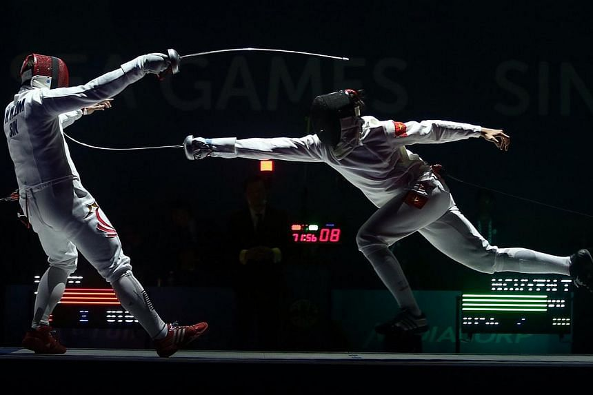 Vietnam's Nguyen Tien Nhat (right) beats Singapore's Lim Wei Wen (left) 15-8 during the finals of the Men's individual épée match held at the OCBC Arena Hall 2 on June 3, 2015. -- ST PHOTO: NEO XIAOBIN