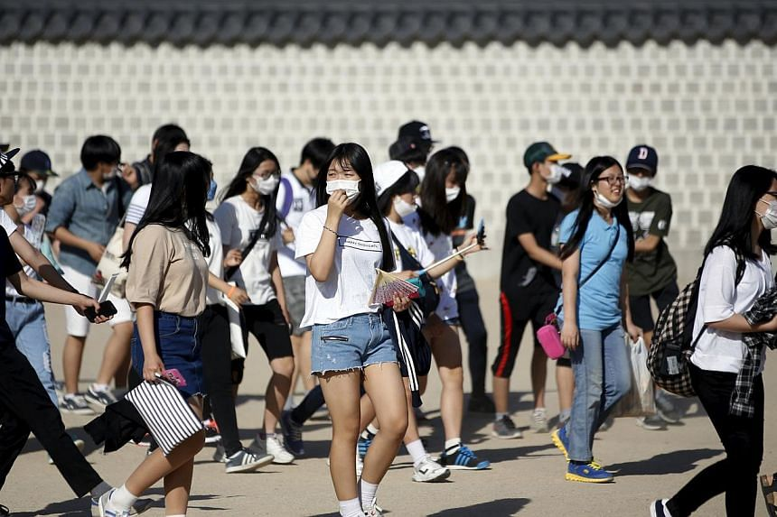 South Korean students wearing masks to prevent contracting Middle East Respiratory Syndrome (MERS) as they walk at the Gyeongbok Palace in central Seoul, South Korea on June 3, 2015. -- PHOTO: REUTERS