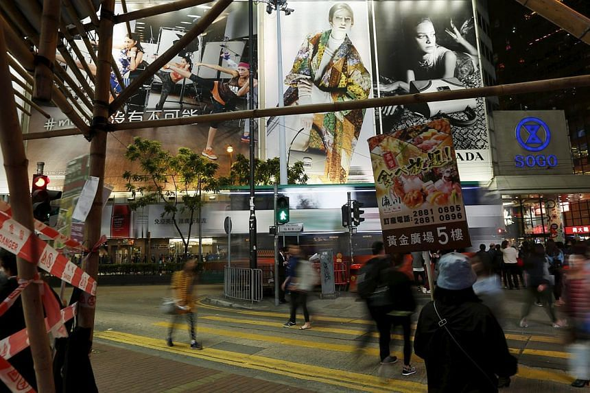 An attendant carries an advertisement of a Japanese restaurant as people cross at street at Causeway Bay shopping district in Hong Kong on March 26, 2015. -- PHOTO: REUTERS