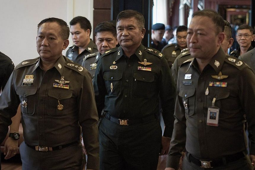 Thai Army Lieutenant General Manas Kongpan (centre) is surrounded by police officers as he turns himself in at the police headquarters in Bangkok on June 3, 2015. -- PHOTO: AFP