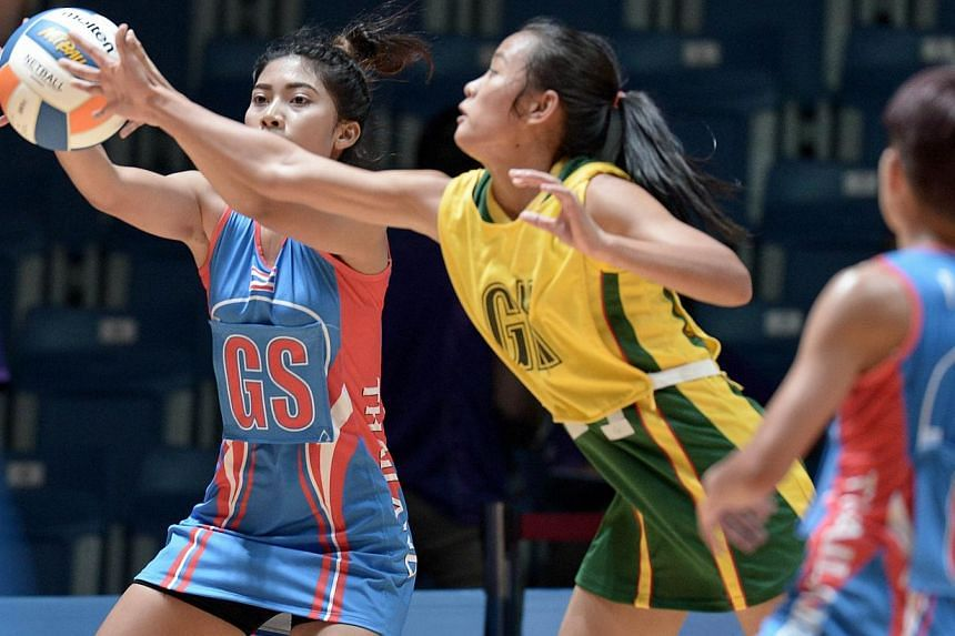 Thailand's Yada Boonkong (left) competes with Myanmar Mon Khin Aye (centre) during the women's netball preliminary round between Thailand and Myanmar at the 28th SEAgames 2015 in Singapore on June 3, 2015. -- PHOTO: AFP