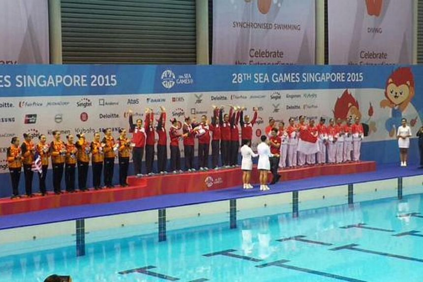 Singapore's synchronised swimmers celebrating at the podium after winning the country's first-ever SEA Games gold medal in the sport on Wednesday evening. -- ST PHOTO: WENG SENG
