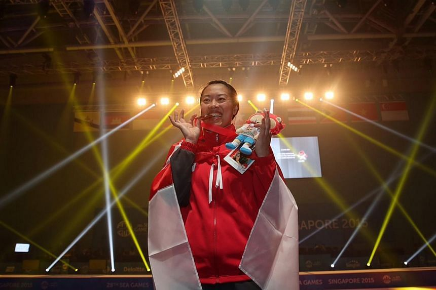 Singapore's Wang Wenying poses for the camera with her gold medal after the prize presentation ceremony for the Women's individual foil match. -- ST PHOTO: NEO XIAOBIN