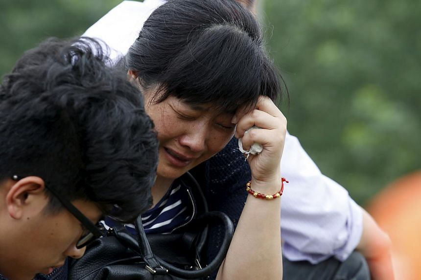 A relative of a passenger of the sunken cruise ship cries on a road to the site of the sinking in the Jianli section of Yangtze River, Hubei province, China, on June 3, 2015. More than 200 divers combed a capsized Chinese ship in the Yangtze Riv