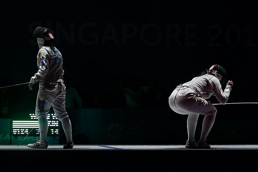 Singapore's Wang Wenying (right) beats Philippines's Justine Gail Tinio (left) 15-7 during the SEA Games fencing Women's individual foil finals held at the OCBC Arena Hall 2 on June 3, 2015. -- ST PHOTO: NEO XIAOBIN
