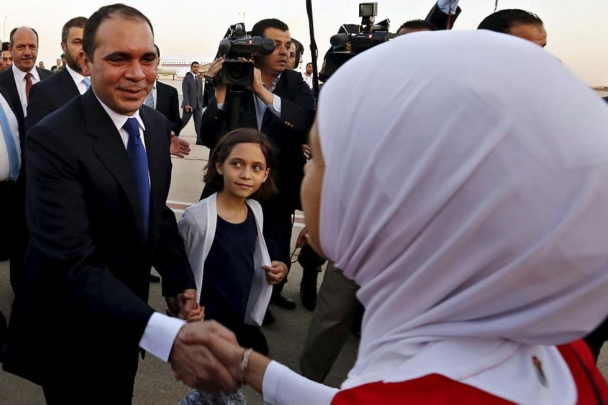Members of the Jordanian women's national soccer team welcome Jordan's Prince Ali bin Al Hussein (left), upon his arrival at Queen Alia International Airport in Amman, after his return from participating in the International Federation of Association