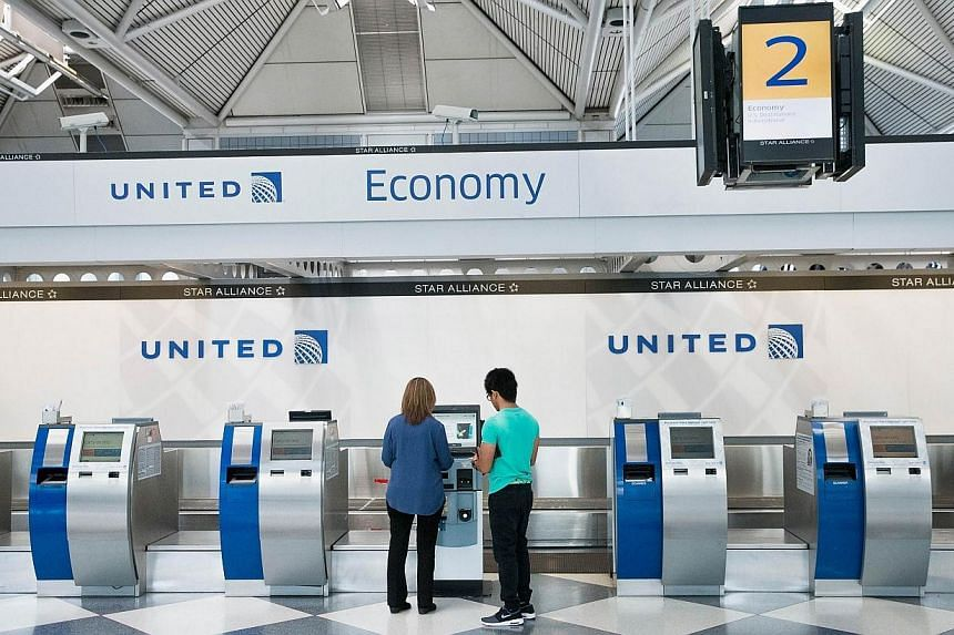 Passengers check-in for flights with United Airlines at O'Hare Airport on Tuesday in Chicago, Illinois. United travelers experienced widespread delays this morning after the airline was forced to ground flights after reports of bomb threats being mad