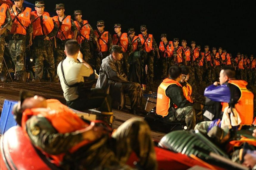 Rescuers walk in a line along the bank side of the Yangtze River as they search for missing passengers of a capsized tourist ship in Jianli, Hubei province, China, late Tuesday (June 2). -- PHOTO: EPA