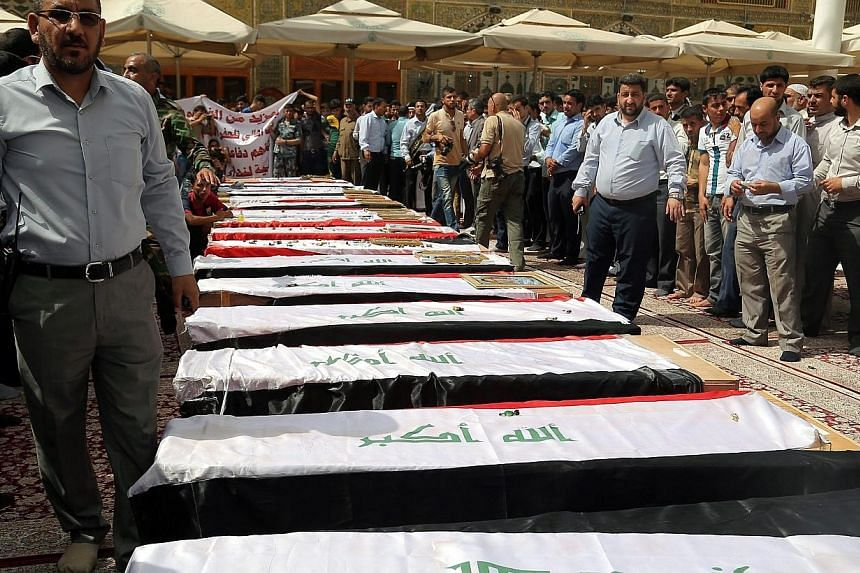 Iraqis stand next to the coffins of Iraqi soldiers believed to have been killed in a suicide attack by ISIS fighters at the base in Tharthar area northern Ramadi, during the funeral processions in Najaf, southern Iraq, on Tuesday (June 2). -- PHOTO: