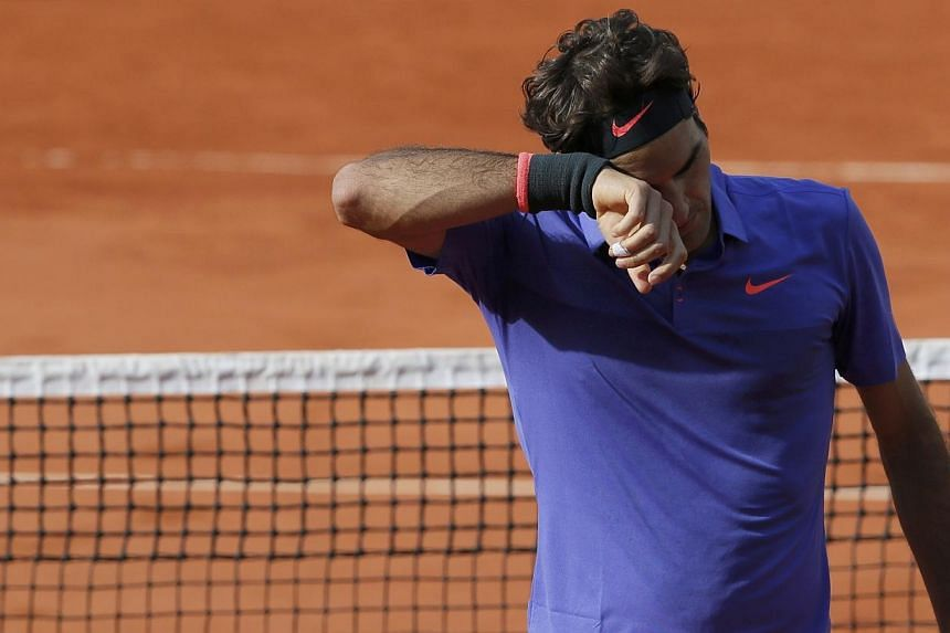 Roger Federer of Switzerland wipes his face during his men's quarter-final match against his compatriot Stan Wawrinka during the French Open tennis tournament at the Roland Garros stadium in Paris on Tuesday (June 2). -- PHOTO: REUTERS