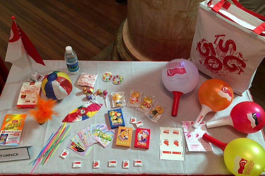 This year's NDP Fun Pack items and a collectible Singa the Lion figurine in each one of the 50 specially designed tote bags.--ST PHOTO: KEVIN LIM