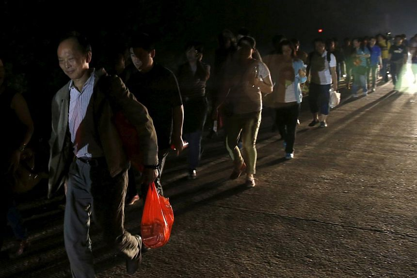 Family members of passengers of a sunken cruise ship marching to the site of the sunken ship in the Jianli section of Yangtze River, Hubei province, China, on June 3, 2015. Dozens of people broke through a police cordon on Wednesday as they marched t