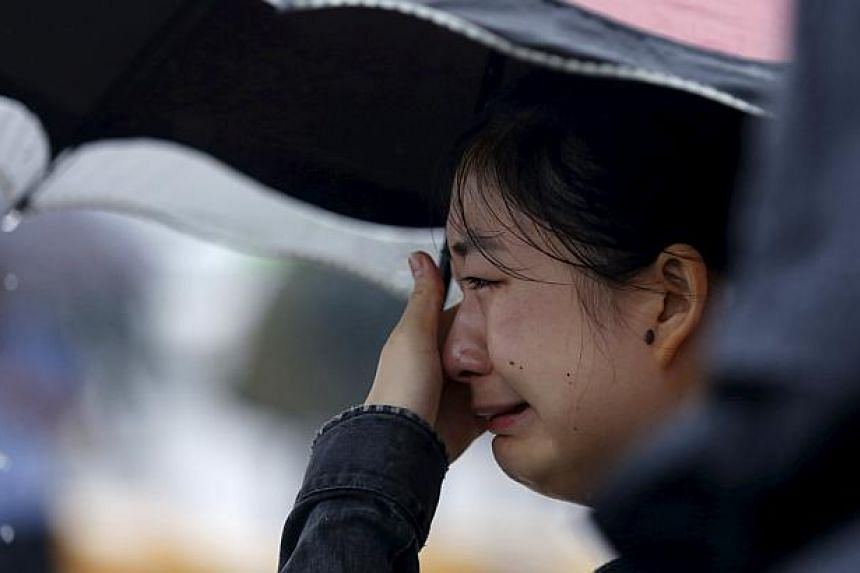 A relative of a missing passenger aboard a capsized ship crying on the banks of the Jianli section of Yangtze River in Hubei province, China, on June 3, 2015. -- PHOTO: REUTERS