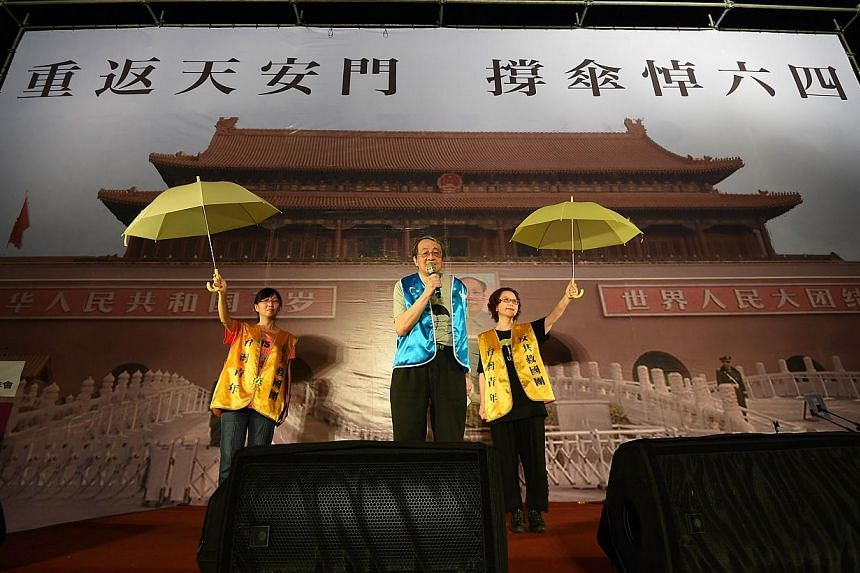 Pro-Taiwan independent activists display a yellow umbrellas in front of a poster showing Beijing's Tiananmen square during a candlelit vigil in Taipei on June 4, 2015. -- PHOTO: AFP