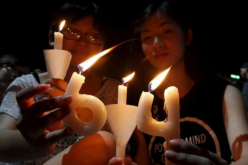 """Pro-democracy supporters hold candles in the shape of """"64"""", which symbolizes """"June 4"""", during an annual candlelight vigil at Victoria Park in Hong Kong. -- PHOTO: REUTERS"""