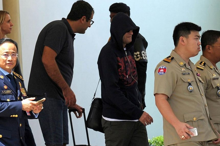 A refugee (third from right) held under Australian custody is escorted by Cambodian police following his arrival at the Phnom Penh International airport on June 4, 2015. -- PHOTO: AFP