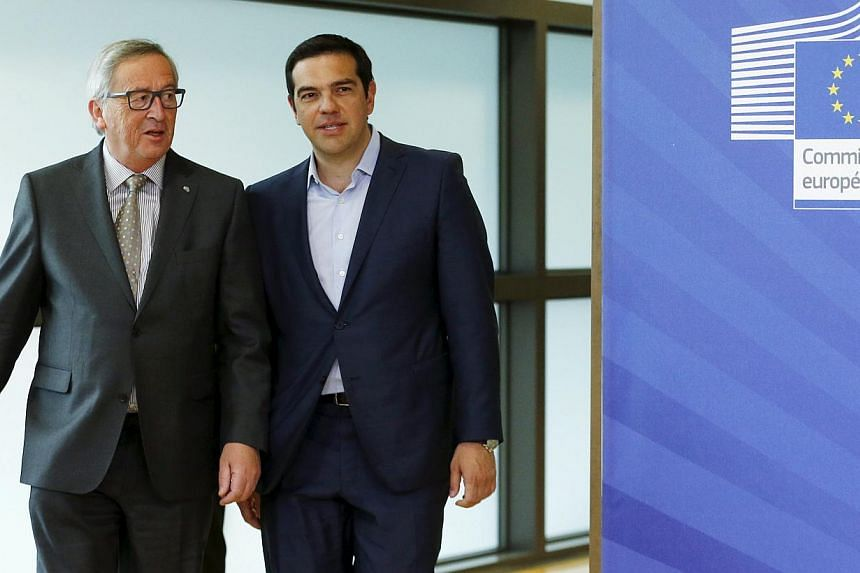 Greek Prime Minister Alexis Tsipras walks with European Commission President Jean-Claude Juncker (left) ahead of a meeting at the EU Commission headquarters in Brussels, Belgium, on June 3, 2015. -- PHOTO: REUTERS
