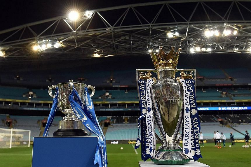 The Capital One cup (left) and English Premier League trophy are displayed as players from Chelsea take part in a football training session in Sydney on June 1, 2015. English Premier League clubs generated record combined revenues of £3.26 billion (