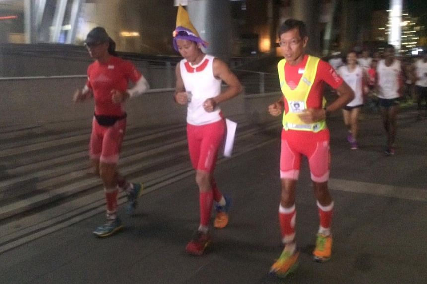 Ultra-marathoners (left to right) Yong Yuen Cheng, pacer Gerrard Lin and Lim Nghee Huat start off their last leg of their 50km daily run over 50 days outside ION orchard with more than 20 runners behind them. -- ST PHOTO: SEAH KWANG PENG