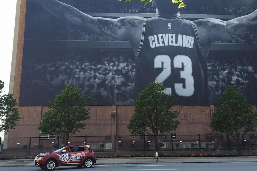 A photograph of downtown Cleveland with a banner of LeBron James in the background. -- ST PHOTO: PAUL ZACH