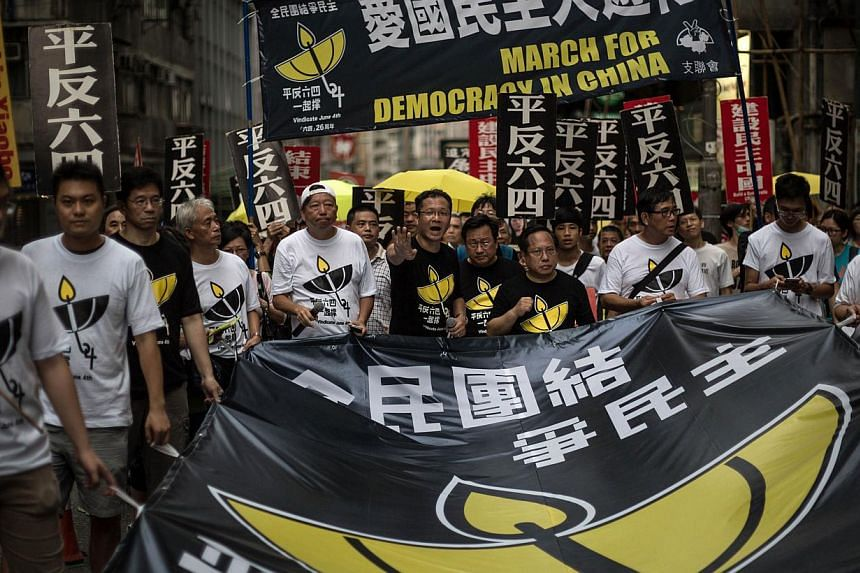 Members of the pro-democracy movement hold a huge banner as they attend a rally in Hong Kong on May 31, 2015, to commemorate the 1989 crackdown at Tiananmen Square in Beijing, prior to the incident's 26th anniversary on June 4. -- PHOTO: AFP