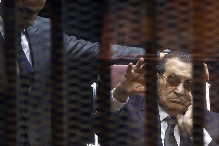 Ousted Egyptian president Hosni Mubarak (right) waves from the defendant's cage next to one of his son's Gamal as they listen to the verdict in their hearing in a retrial for embezzlement in Cairo on May 9, 2015. Egypt's high court said on Thursday
