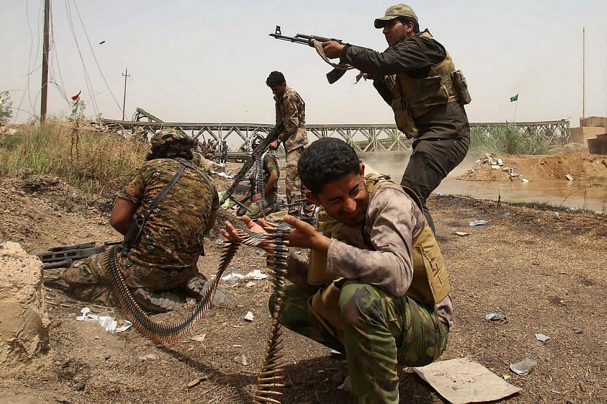 Members of the Popular Mobilisation units opens fire during a fight with ISIS militants in the area of Sayed Ghareeb, near Dujail, some 70km north of Baghdad, on May 28, 2015. -- PHOTO: AFP
