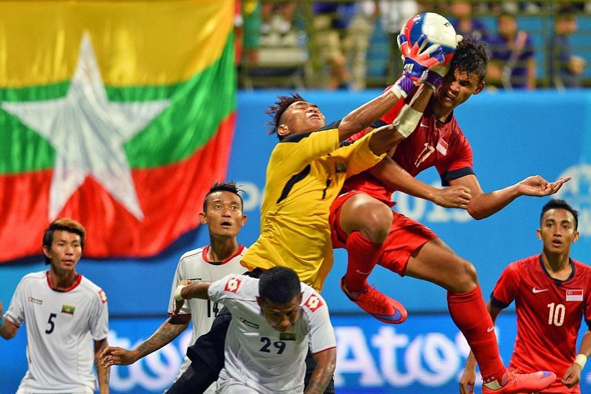 Myanmar's goalkeeper Phyo Kyaw Zin challenges Singapore's Irfan Fandi Ahmad (in red, no.17) for the ball in the Singapore VS Myanmar football match of the 28th SEA Games played at Jalan Besar Stadium on June 4, 2015. Myanmar won the match 2-1. -