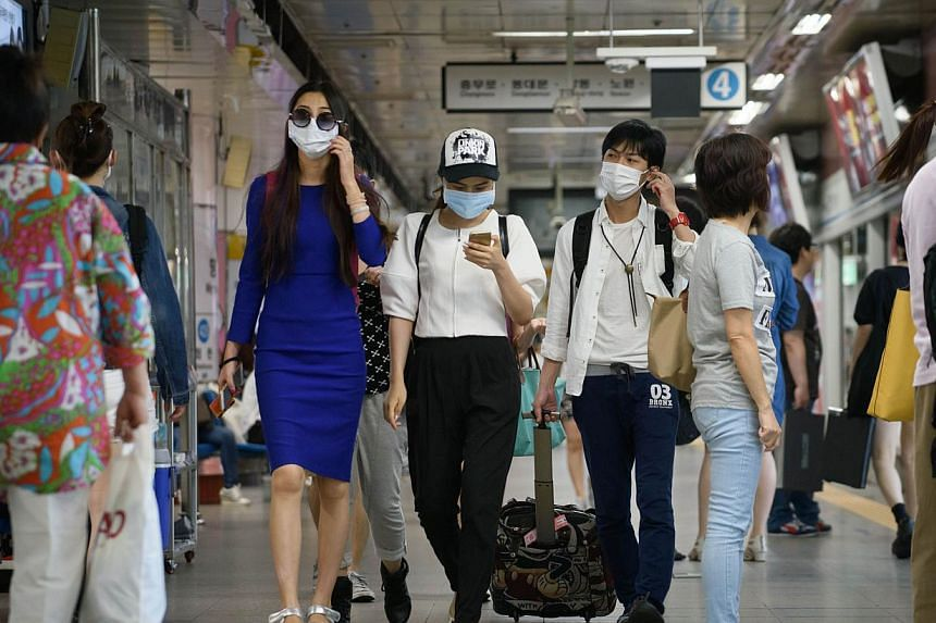 People wearing face masks walk through a subway station in the popular Myeongdong shopping area in Seoul on June 4, 2015. South Korea has reported a third fatality in a Mers virus outbreak that has fuelled growing alarm in the country. -- PHOTO: AFP