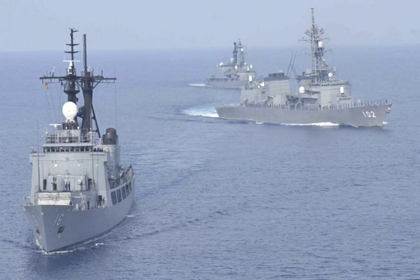 Japanese Maritime Self-Defence Force destroyers Harusame (right) and Amagiri (background) sail near Philippine warship BRP Ramon Alcaraz (foreground) during a joint naval drill in South China Sea on May 12, 2015. Japan and the Philippines were set to