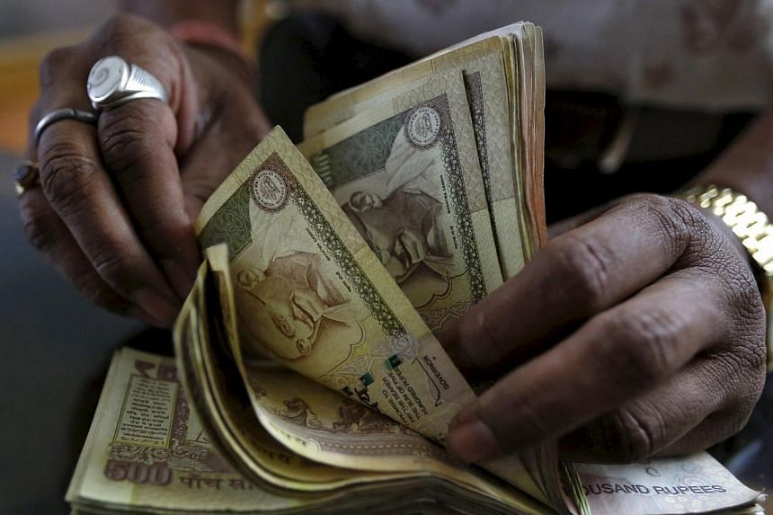 A money lender counts Indian rupee currency notes at his shop in Ahmedabad, India. -- PHOTO: REUTERS
