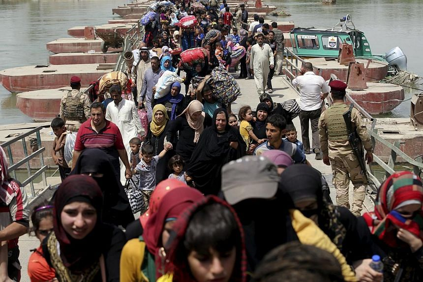 Displaced Sunni people fleeing the violence in Ramadi, cross a bridge on the outskirts of Baghdad on May 24, 2015. The United Nations is appealing for US$497 million (S$670 million) to pay for shelter, food and water over the next six months for 5.6