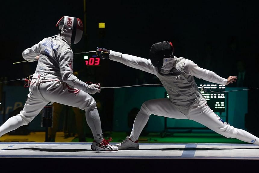 Thailand's Panchan Nontapat (right) beats Singapore's Kevin Jerrold Chan 15-6 in the SEA Games fencing men's individual foil semifinals held at the OCBC Arena Hall 2 on June 4, 2015.-- ST PHOTO: NEO XIAOBIN