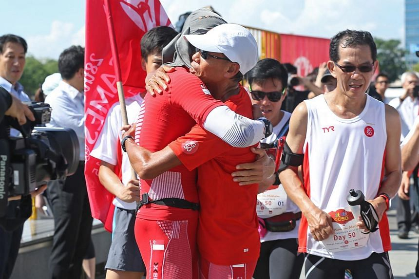 Ultramarathoners (centre) Lim Nghee Huat and (left) Yong Yuen Cheng hug each other upon crossing the finish line at the Promontory after running 10 loops around Marina Bay on their last leg of running 50km every day for 50 days. -- ST PHOTO: SEAH KWA