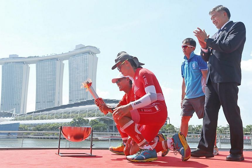 Ultramarathoners (left) Lim Nghee Huat and (second from left) Yong Yuen Cheng light up the SEA Games flame at the Promontory, as (right) Lim Teck Yin (Singapore Southeast Asian Games Organising Committee (SINGSOC) Executive Committee (EXCO) Chairman)
