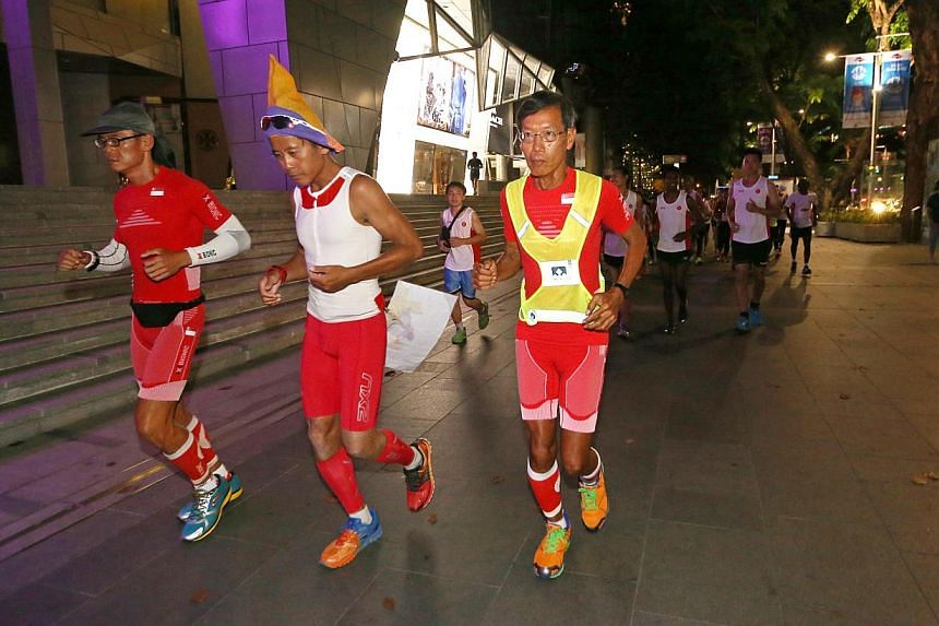 Ultramarathoners Yong Yuen Cheng (left) and Lim Nghee Huat (right) with pacer Gerrard Lin, on their last leg of running 50km for 50 days. -- ST PHOTO: SEAH KWANG PENG