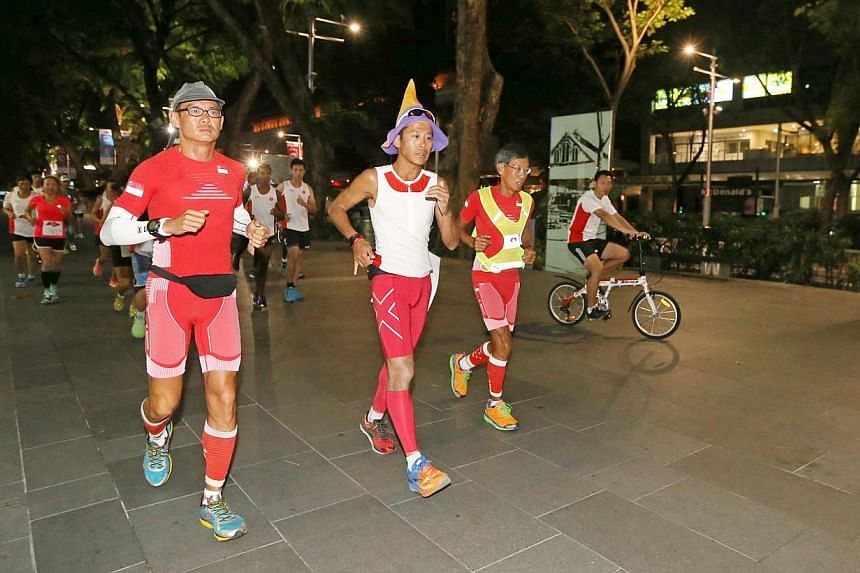 Ultramarathoners Yong Yuen Cheng (left) and Lim Nghee Huat (second, right) with pacer Gerrard Lin (second, left), on their last leg of running 50km for 50 days.-- ST PHOTO: SEAH KWANG PENG