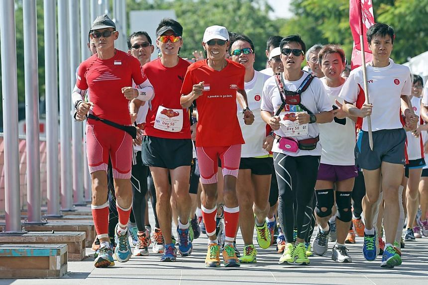 Ultramarathoners (second from left) Lim Nghee Huat and (left) Yong Yuen Cheng and their support runners near the finish line after running 10 loops around Marina Bay on their last leg of running 50km every day for 50 days. -- ST PHOTO: SEAH KWANG PEN