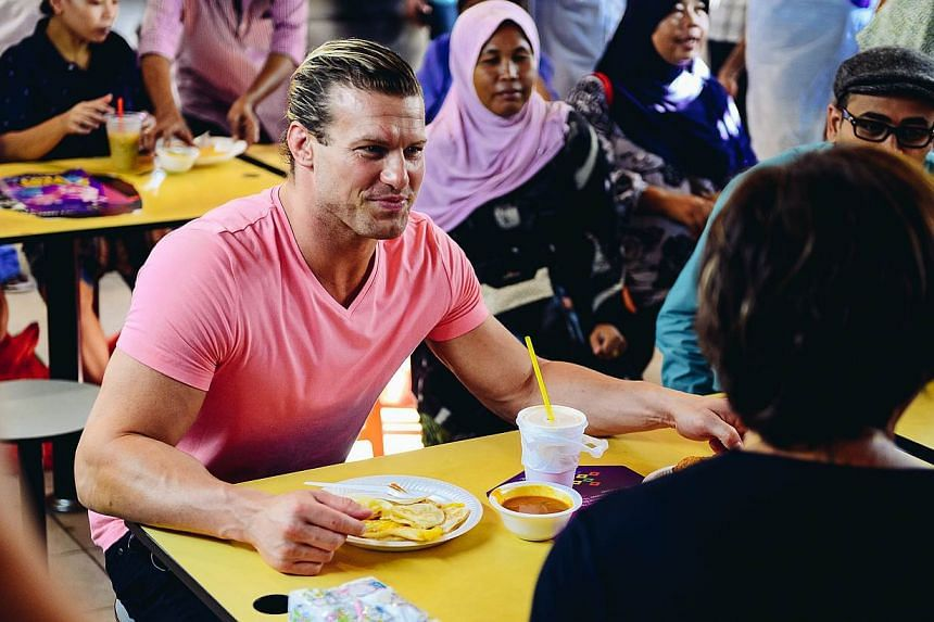 WWE Superstar Dolph Ziggler tucks into roti prata at Tekka Market on May 29, 2015. -- PHOTO: WWE