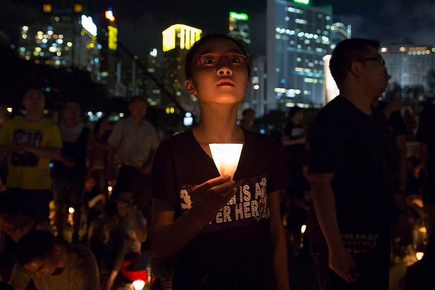 People take part in a candlelight vigil in Hong Kong on June 4, 2015, to mark the crackdown on the pro-democracy movement in Beijing's Tiananmen Square in 1989. -- PHOTO: AFP