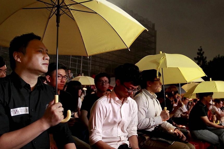 Chinese dissident Wang Dan (left) holds a yellow umbrella, a symbol of Hong Kong's Occupy Central pro-democracy movement, during a night vigil at Liberty Square in Taipei, Taiwan, on June 4, 2015. -- PHOTO: REUTERS