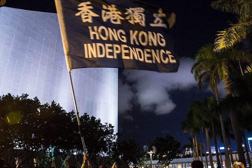 """A pro-democracy activist waves a flag that reads """"Hong Kong Independence"""" during the commemoration of China's 1989 Tiananmen Square crackdown in the Tsim Sha Tsui district of Hong Kong on June 4, 2015. -- PHOTO: AFP"""