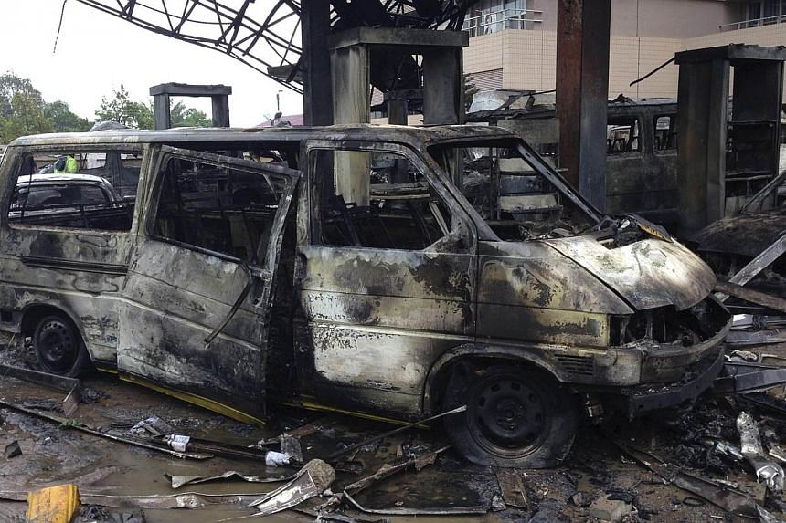 The charred wreckage of a minivan is seen at a gas station that exploded overnight killing around 90 people in Accra, Ghana, on June 4, 2015. An explosion at a petrol station in Ghana's capital killed about 90 people, many of whom had sought she