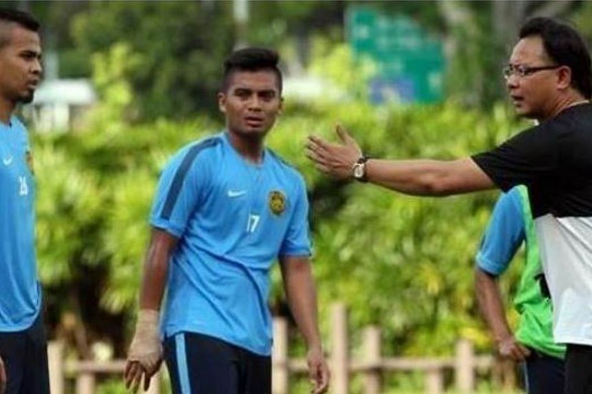 Malaysian national football coach Ong Kim Swee (right) giving instructions to his players during their training at the ITE Sports Complex in Singapore on May 28, 2015. Ong's men are on the verge of elimination from the SEA Games, after a 5-1 drubbing