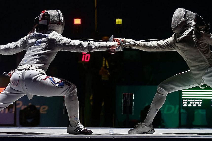 Thailand's Starrat Sirawalai (left) beats Singapore's Ywen Lau 15-13 in the SEA Games fencing women's individual sabre semifinals held at the OCBC Arena Hall 2 on June 4, 2015. The Singapore fencers ended their individual campaigns after winning